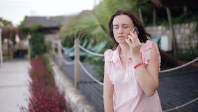 Mulher que sorri e que fala no telefone perto do café na praia video estoque