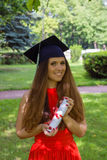 Mulher que sorri em sua graduação contra o nascer do sol sobre árvores Imagem de Stock
