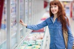Mulher que sorri na câmera ao fazer compras na mercearia fotos de stock