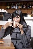 Mulher que sorve o chocolate quente em um coffeeshop Fotografia de Stock Royalty Free