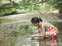 Mulher que Squatting em Forest Lake With Hands Cupped imagens de stock