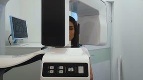 Mulher que submete-se ao exame panorâmico do raio X, equipamento radiográfico profissional filme