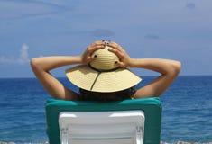 Mulher que sunbathing em uma cadeira plástica em um bonito Fotografia de Stock Royalty Free
