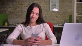 Mulher que surfa o smartphone e para mudar as emoções do atonishment negativo aos tendernes vídeos de arquivo