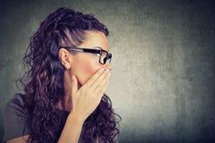 Mulher que sussurra a informação privada um segredo foto de stock royalty free