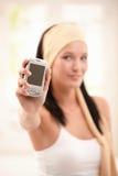 Mulher que sustenta o telefone móvel no foco Fotografia de Stock