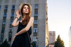 Mulher que sustenta seu chapéu e que olha afastado no fundo da construção na noite do por do sol fotografia de stock royalty free