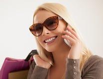 Mulher que telefona ao comprar Fotografia de Stock Royalty Free