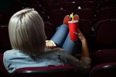 Mulher que tem bebidas ao olhar o filme no teatro fotos de stock