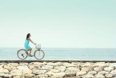 Mulher que tem a bicicleta da equitação do divertimento na praia fotos de stock