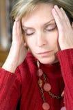 Mulher que tem a dor de cabeça fotografia de stock