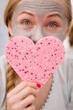 Mulher que tem a máscara protetora cinzenta que guarda a esponja do coração imagem de stock royalty free