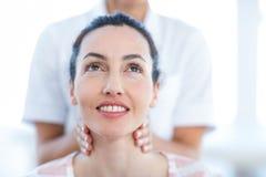 Mulher que tem a massagem da garganta imagens de stock royalty free