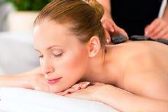 Mulher que tem a massagem de pedra quente dos termas do bem-estar Fotografia de Stock