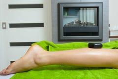 Mulher que tem a massagem dos pés com pedras quentes Fotos de Stock Royalty Free