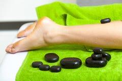 Mulher que tem a massagem dos pés com pedras quentes Imagem de Stock