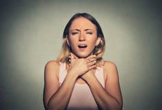 A mulher que tem o ataque de asma ou que bloqueia não pode respiração Fotos de Stock Royalty Free