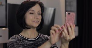 Mulher que tem o bate-papo em meios sociais usando o smartphone que aprecia a conversa ao amigo imagens de stock royalty free