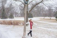 Mulher que tem o divertimento que balança em torno do cargo da lâmpada no parque quando s fresco imagens de stock