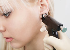Mulher que tem o processo piercing da orelha com equipamento especial Imagens de Stock Royalty Free