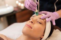 Mulher que tem o tratamento do facial do microdermabrasion foto de stock