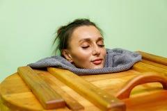 Mulher que tem o tratamento dos termas na sauna de madeira do tambor, banheira do cedro foto de stock