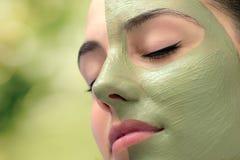 Mulher que tem o tratamento facial cosmético da alga nos termas foto de stock