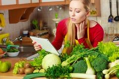Mulher que tem os vegetais verdes que pensam sobre o cozimento Fotografia de Stock