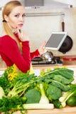 Mulher que tem os vegetais verdes que pensam sobre o cozimento Fotos de Stock