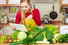 Mulher que tem os vegetais verdes que pensam sobre o cozimento Imagem de Stock