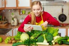 Mulher que tem os vegetais verdes que pensam sobre o cozimento Imagens de Stock
