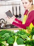 Mulher que tem os vegetais verdes que pensam sobre o cozimento Foto de Stock