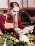 Mulher que tem os vegetais verdes que pensam sobre o cozimento Imagens de Stock Royalty Free
