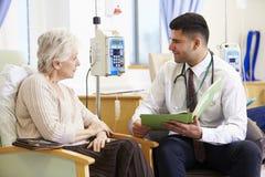 Mulher que tem a quimioterapia com doutor Looking At Notes Imagem de Stock