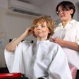 Mulher que tem seu corte do cabelo Fotografia de Stock Royalty Free