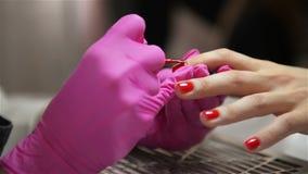 Mulher que tem um tratamento de mãos do prego em um salão de beleza com uma opinião ascendente próxima um esteticista Applying Va vídeos de arquivo