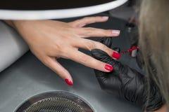 Mulher que tem um tratamento de mãos do prego em um salão de beleza com uma opinião do close up um esteticista que aplica o verni foto de stock royalty free