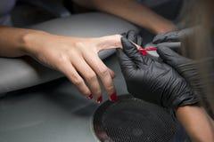 Mulher que tem um tratamento de mãos do prego em um salão de beleza com uma opinião do close up um esteticista que aplica o verni imagem de stock