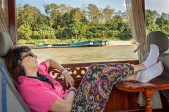 Mulher que tem uma sesta em um barco ao cruzar em Nam Kahn River fotografia de stock royalty free