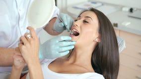 Mulher que tem uma verificação acima na cirurgia do dentista video estoque