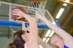Mulher que tenta disparar na bola na rede Imagem de Stock Royalty Free