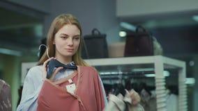 Mulher que tenta na roupa na loja de roupa Make para escolher o vermelho do betvine e vídeos de arquivo