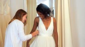 Mulher que tenta no vestido de casamento com a ajuda do desenhador de moda video estoque