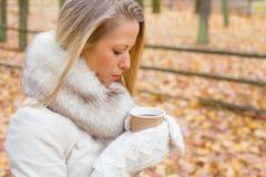 Mulher que tenta refrigerar para baixo seu café Fotografia de Stock Royalty Free