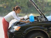 Mulher que tenta reparar o carro Fotos de Stock Royalty Free