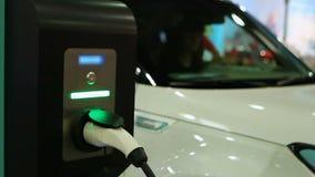 Mulher que testa o carro bonde na feira automóvel, veículo ligado ao ponto de carregamento video estoque