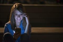 Mulher que texting Menina bonita alegre de sorriso feliz nova da mulher do close up que olha a leitura móvel do telefone celular  Foto de Stock