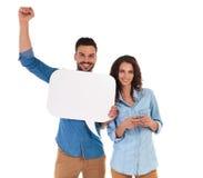 A mulher que texting quando o homem guardar a bolha do discurso e comemora succes imagens de stock royalty free