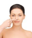 Mulher que toca em seu nariz Foto de Stock
