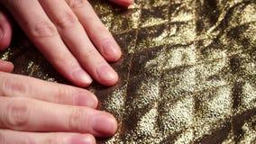 A mulher que toca em uma tela de nylon lisa, dourada do poliéster no matérias têxteis compra vídeos de arquivo